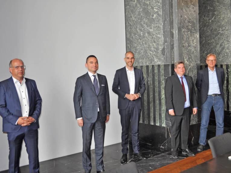 Fünf Männer in einem Saal.