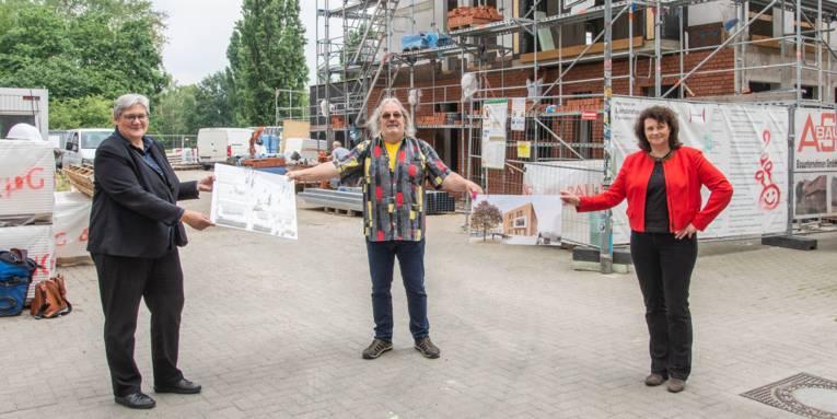 Zwei Frauen und ein Mann stehen vor einem Gebäuderohbau und präsentieren mit einem Modell und einem Schaubild, wie das Gebäude nach der Fertigstellung aussehen soll
