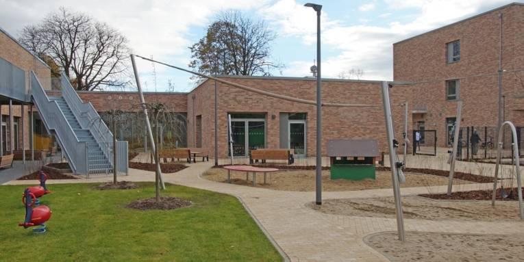 Leerer Hof der Kita und Grundschule am Welfenplatz. Zwischen den Gebäuden stehen Bänke und Spielgeräte.