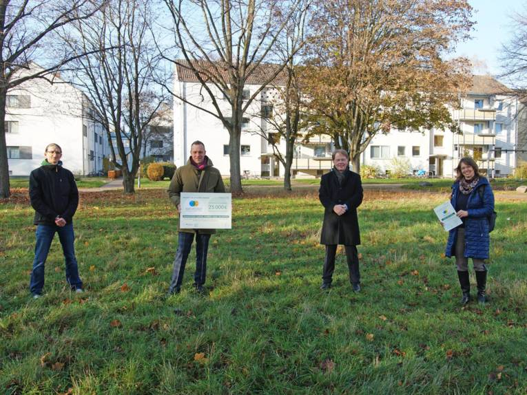 Vier Personen auf einer Rasenfläche. Sie halten eine Art Scheck in die Kamera.