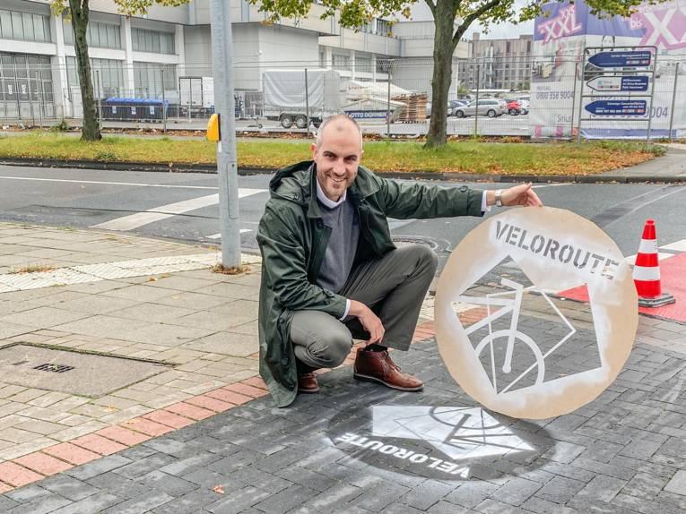 """OB Onay hockt auf einem Radfahrstreifen und hält eine Sprühschablone mit der Aufschrift """"Veloroute"""" und einem Fahrrad-Piktogramm in der Hand"""