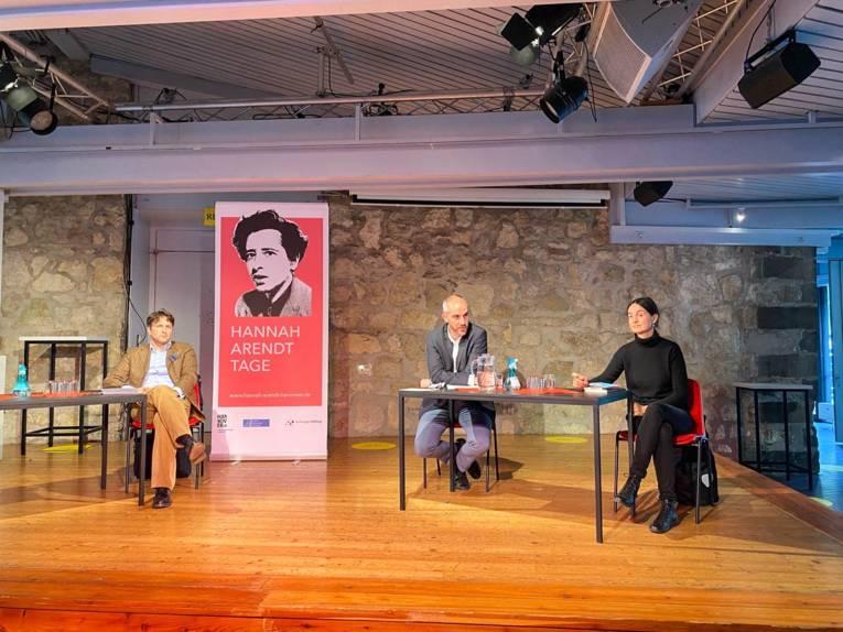 Drei Personen auf einer Bühne.