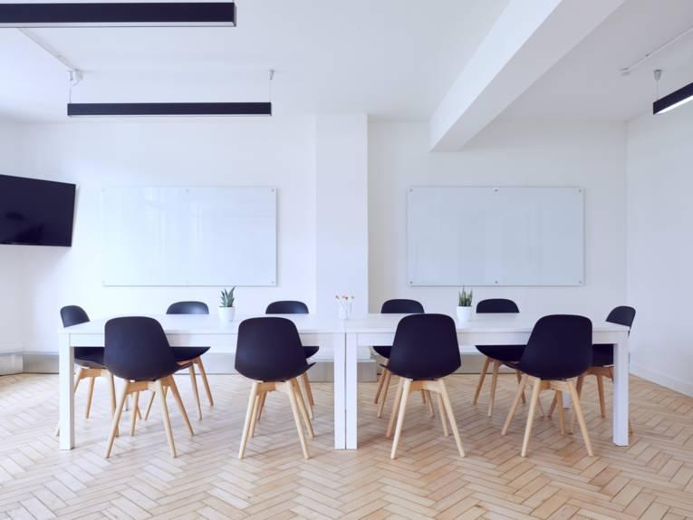 Ein Besprechungstisch, um den herum mehrere Stühle stehen
