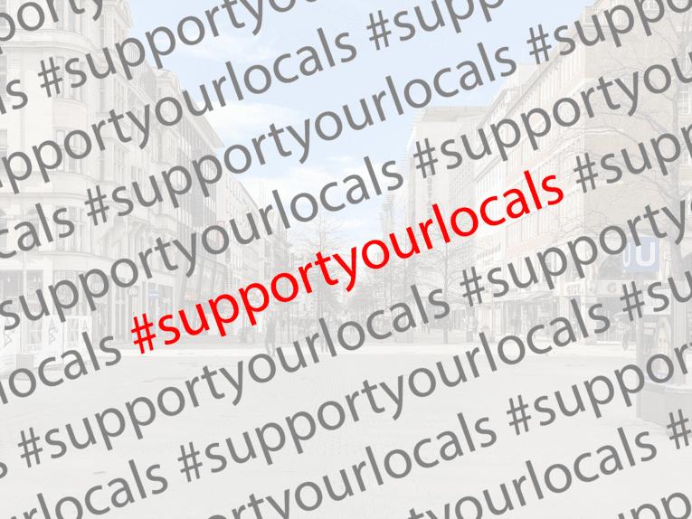 Aufnahme einer Einkaufsstraße blass im Hintergrund, im Vordergrund mehrfach der Text #supportyourlocals
