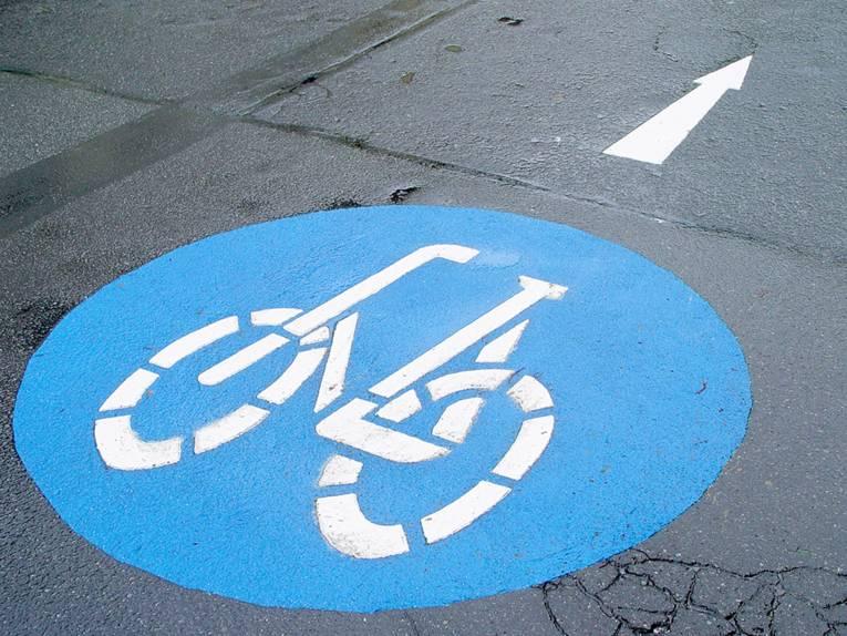 Ein weißer Strichmännchen-Radfahrer auf blauem Grund