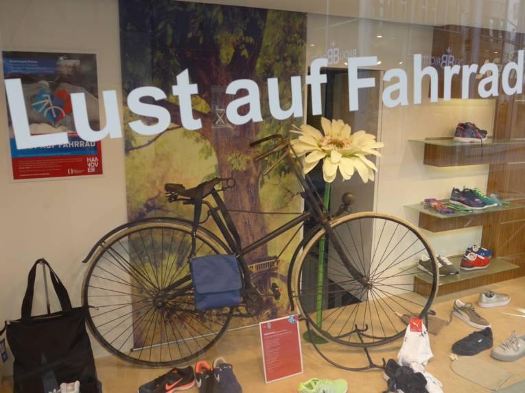 Das Schaufenster eines Ladens, mit Schuhen in der Auslage und ein altes Fahrrad dient der Dekoration.