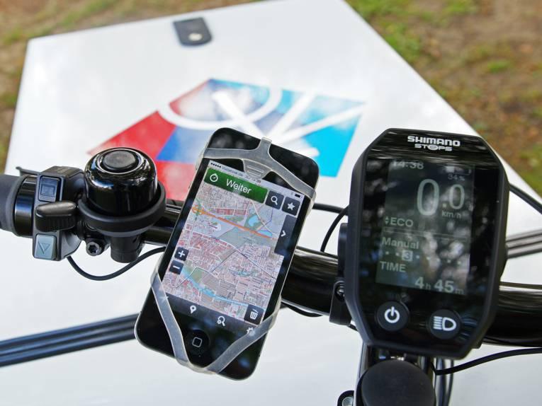 Ein Fahrradlenker, an dem ein Smartphone mit Karte angebracht ist