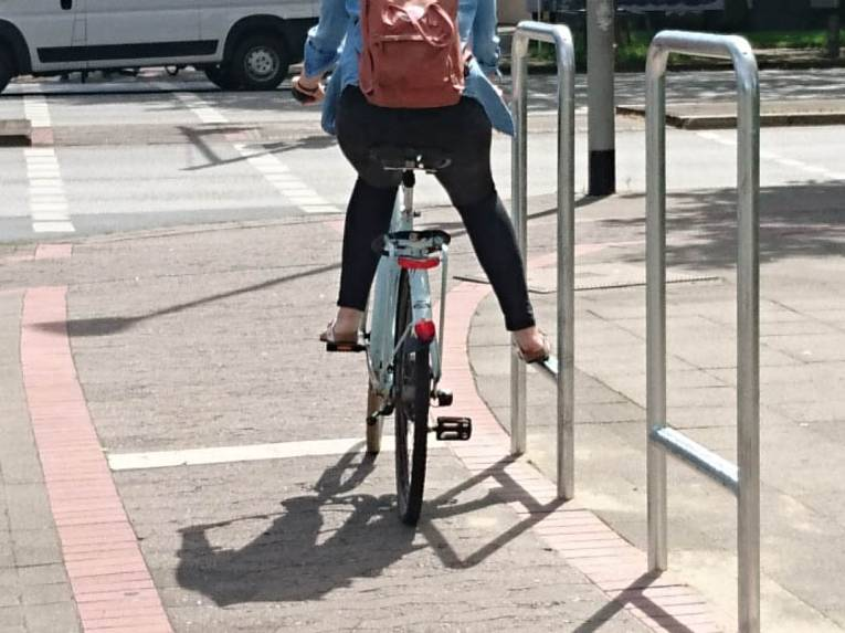 Fahrradfahrerin, die ihr Bein auf einer Trittstange abstellt.
