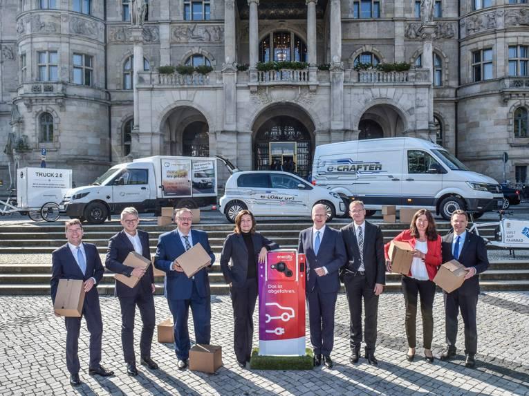 Die Repräsentanten der Partner zum Start der Initiative Urbane Logistik Hannover vor dem neuen Rathaus mit verschiedenen Fahrzeugen im Hintergrund.