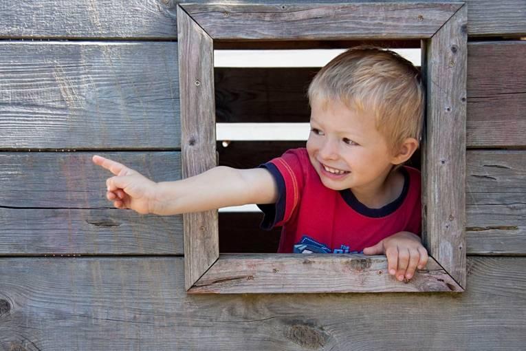 Ein Junge zeigt aus einem Holzfenster.