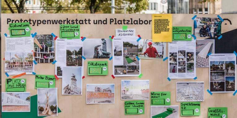 """Auf einer Holzwand im Freien mit der Überschrift """"Prototypenwerkstatt und Platzlabor"""" sind zahlreiche Bilder und Vorschläge zur Umgestaltung des Steintorplatzes befestigt."""