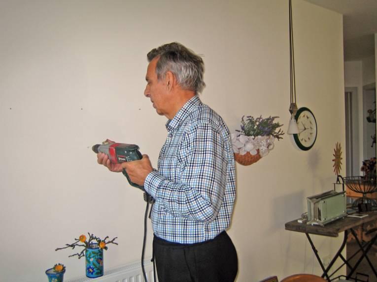 Ein älterer grauhaariger Mann bohrt ein Loch in eine Wand