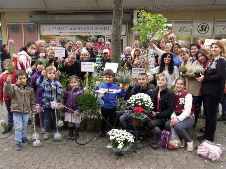 Ein große Anzahl Bewohnerinnen und Bewohner verschiedenen Alters aus dem Sahlkamps halten auf dem Gruppenfoto Pflanzen in den Händen.