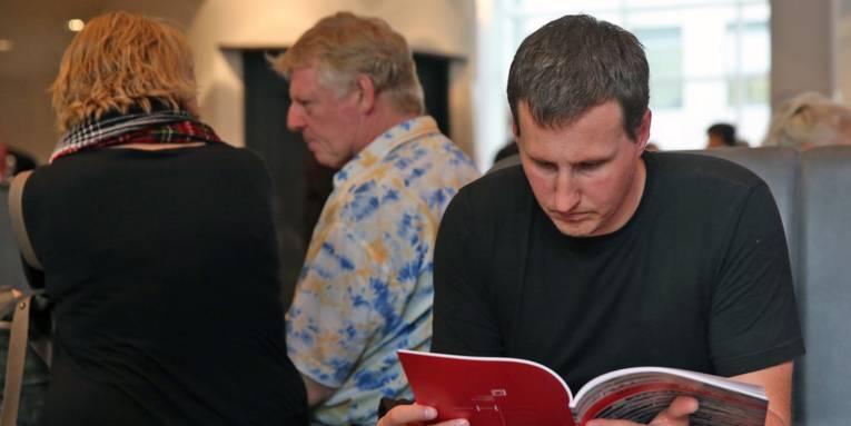 Ein junger Mann, der in einer Broschüre liest.