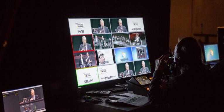 Ein Mann vor einem großen Monitor.
