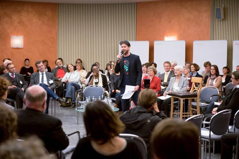 Mann mit Mikrofon vor Publikum stehend.