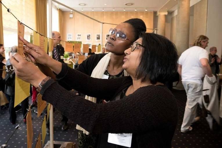 Zwei Frauen, die beschriftete Karteikarten in Augenschein nehmen.