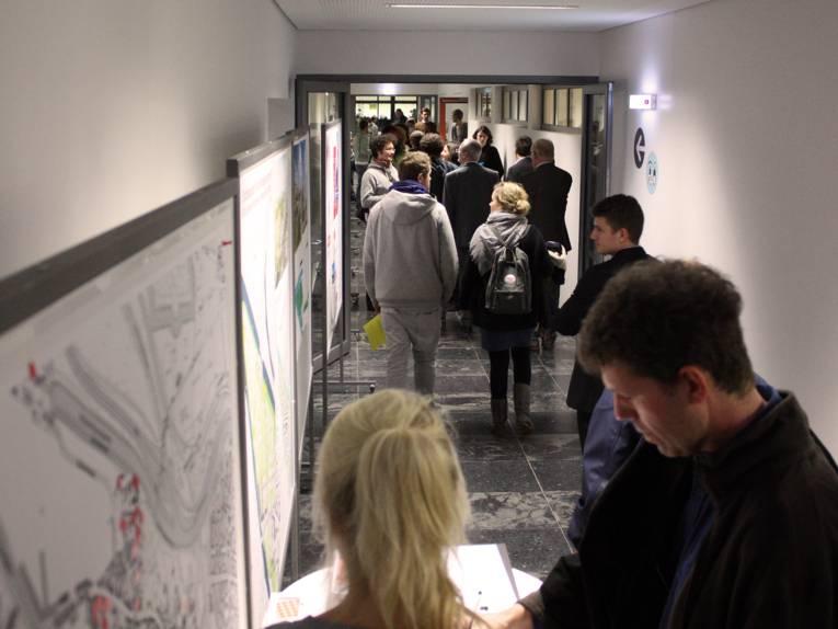 Viele TeilnehmerInnen bewegen sich auf dem Gang, im Vordgrund steht ein Besucher und liest einen Infoflyer