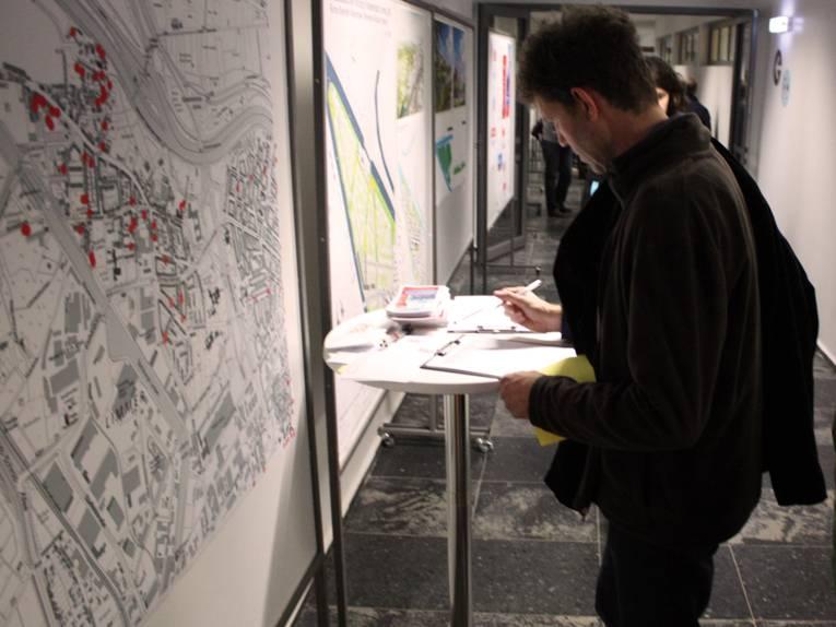 Ein Besucher trägt sich an einem Stehtisch stehend in eine Unterschriftenliste ein