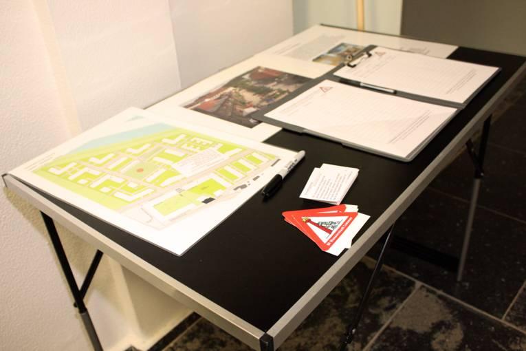 Auf einem Tisch liegen Aufkleber, Listen und Info-Blätter