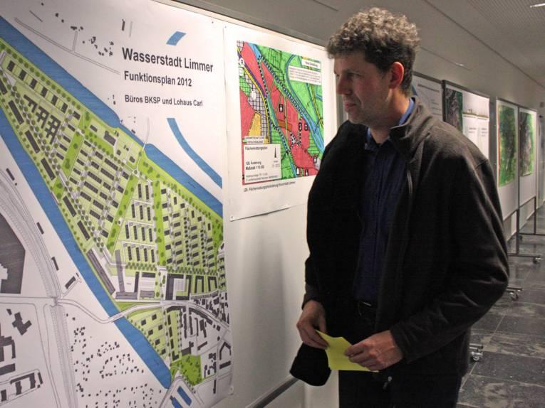 Ein besucher betrachtet einen großen Planungsplan für die Wasserstadt
