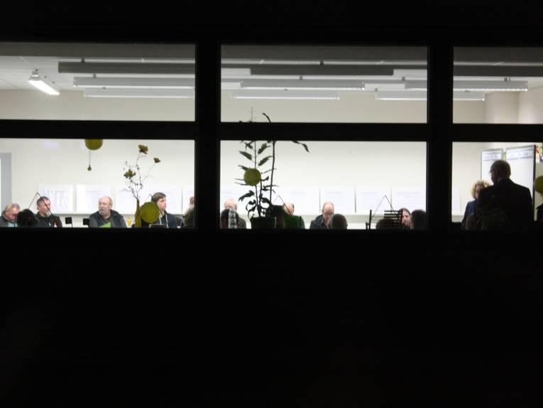 Von außen in einen hell erleuchteten Klassenraum fotografiert; drinnen sitzen einige Menschen im Plenum
