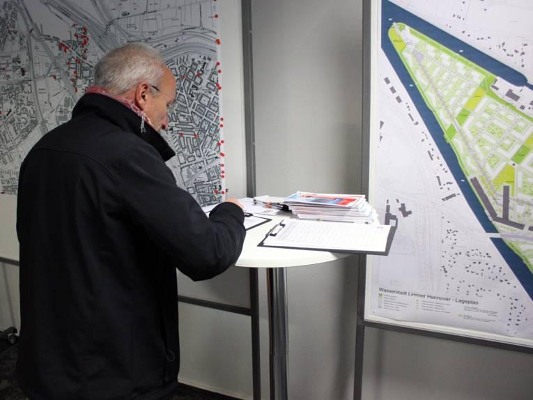 Ein Besucher trägt sich in eine Unterschriftenliste ein