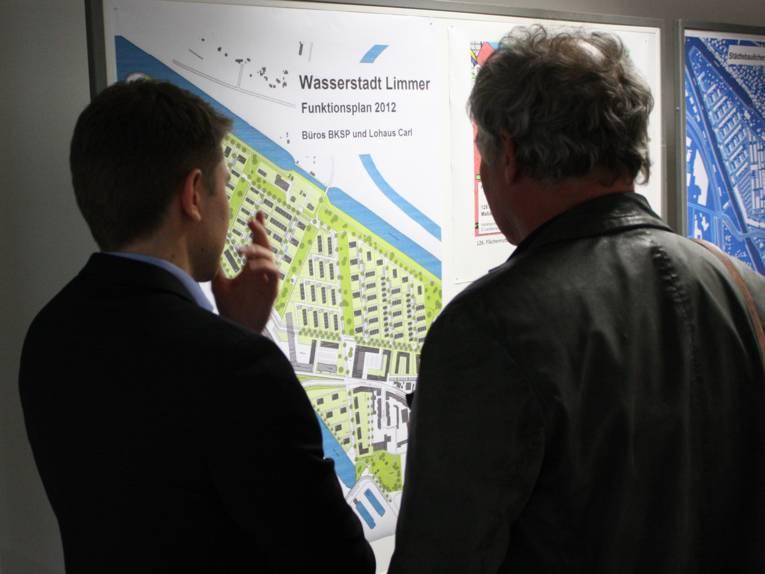 Zwei Herren stehen vor einer Stellwand und diskutieren über den ausgehängten Planungsentwurf