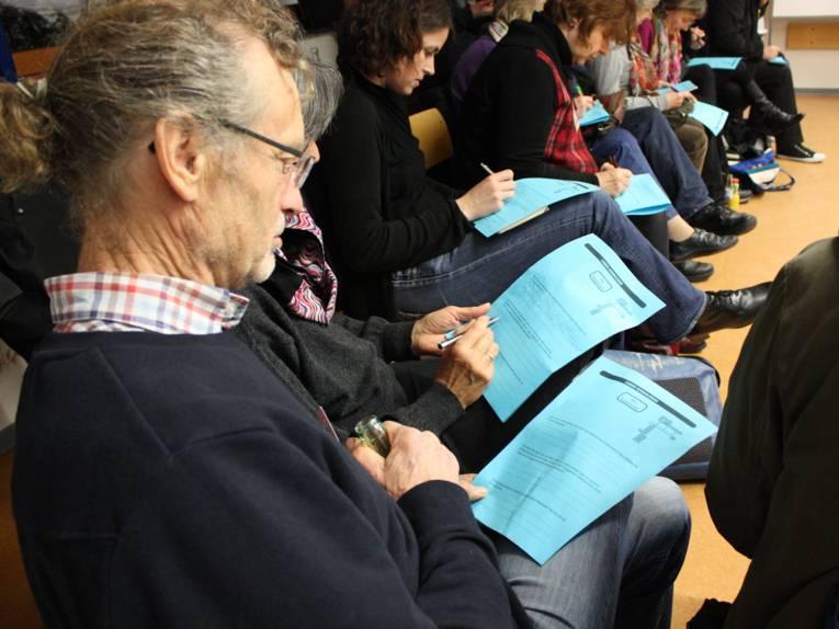 Ein Veranstatlungsteilnehmer liest einen Befragungsbogen