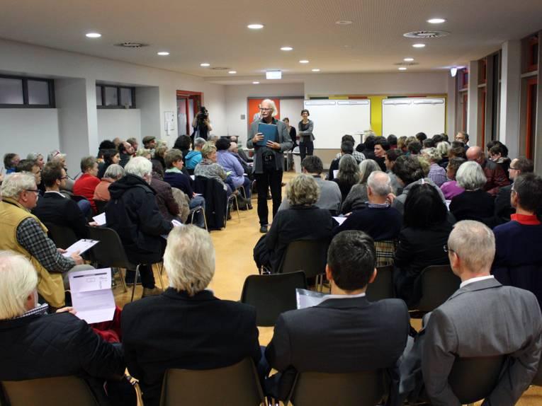 In einem Klassenraum sitzen viele Personen und diskutieren mit einem Moderator innerhalb eines Plenums.