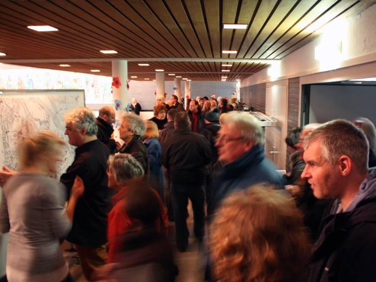 Besucherinnen und Besucher betreten die Aula