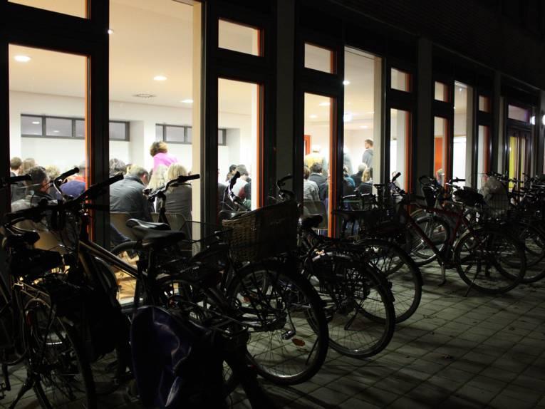 Blick von außen in den hell erleuchteten Klassenraum in dem viele perosnen sitzen.