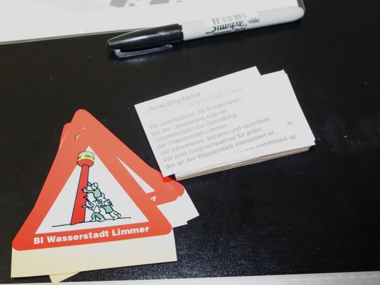 Auf einem Tisch liegen dreieckige Aufkleber der BI Wasserstadt und Infozettel liegen