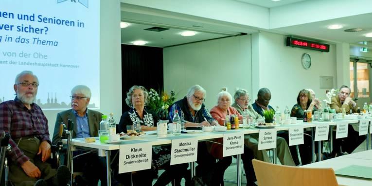 """Die Mitglieder des Seniorenbeirats sitzen vorne in einer Reihe; dahinter ein Stück Projektionsfläche, auf der der Redner, Herr von der Ohe, zum Thema """"Leben Seniorinnen und Senioren in Hannover sicher"""" angekündigt wird."""