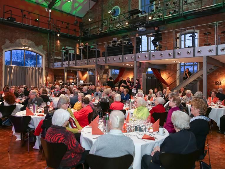 Im Restaurant Cavallo, der umgebauten königlichen Reithalle in der Dragonerstraße, sitzen an vielen Tischen festlich gekleidete ältere Menschen und genießen bei Essen und Trinken ein Showprogramm.