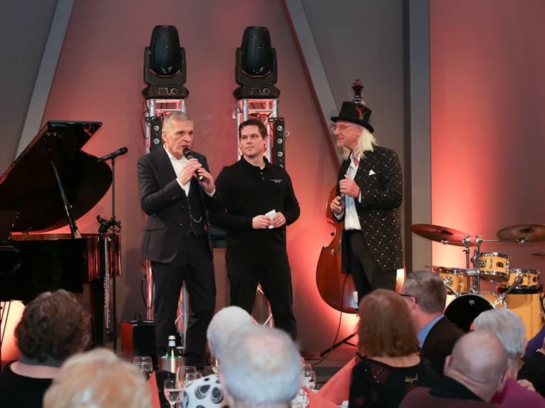 Drei Herren auf einer Bühne, daneben ein Klavier und ein Schlagzeug; vor der Bühne sitzt ein älteres Publikum.