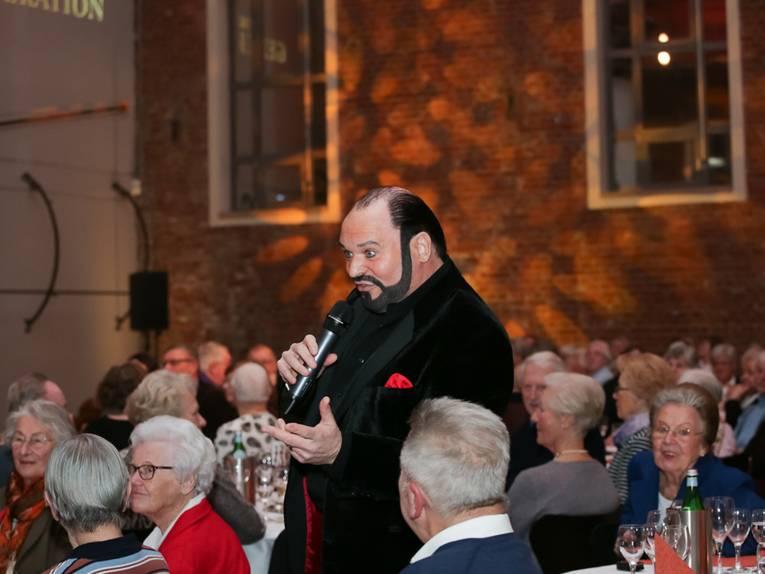 Ein Sänger im schwarzen Anzug singt im Publikum.