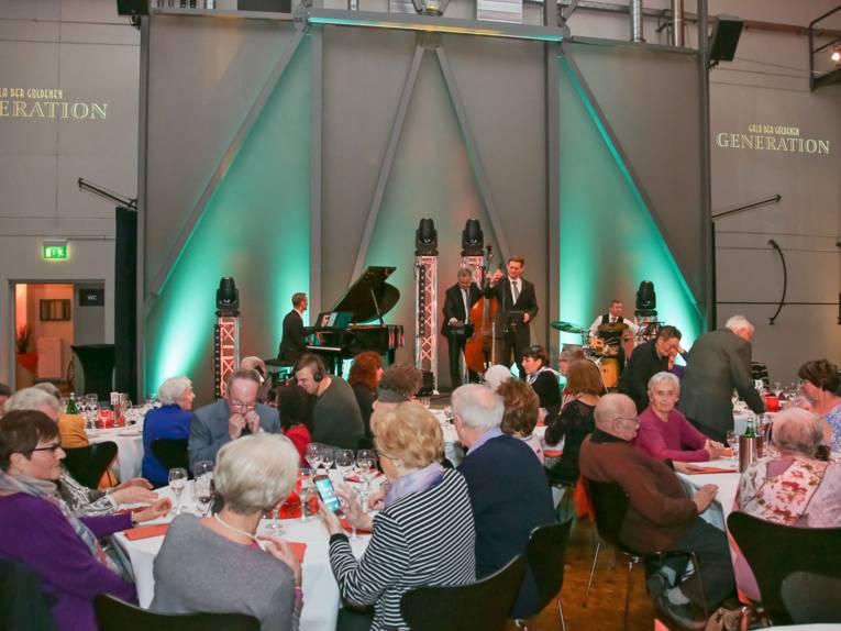 An mehreren Tischen sitzen ältere Herrschaften; auf der Bühne spielt die Band The Ellingstones