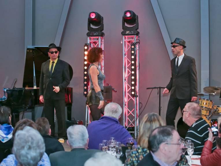 Zwei Schauspieler in Anzügen, mit Sonnenbrille und Hut auf der Bühne, dazwischen eine Tänzerin.