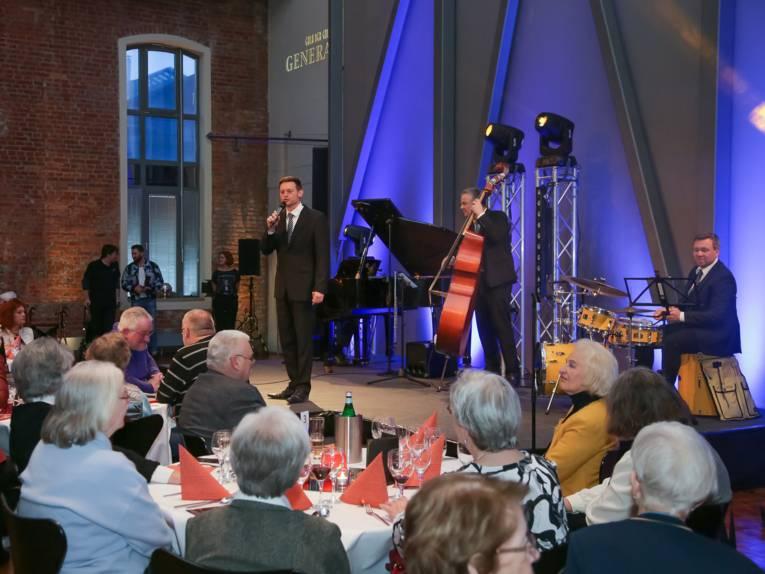 Drei Musiker in schwarzen Anzügen (Sänger, Cellist, Schlagzeuger) spielen auf der Bühne vor älterem Publikum.
