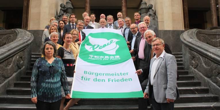 """Etwa 30 Personen stehen auf der inneren Rathaustreppe und halten gemeinsam die ausgebreitete Fahne """"Mayors for Peace - Bürgermeister für den Frieden"""""""