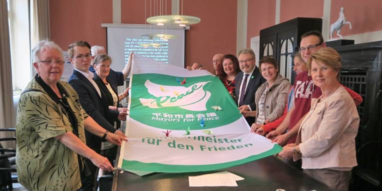 Über einen Tisch im Neuen Rathaus hält eine Gruppe von Menschen gemeinsam mit Bürgermeister Thomas Hermann die Mayors for Peace Fahne, die eine weiße Friedenstaube zeigt. Darauf befinden sich einige Papierkraniche.