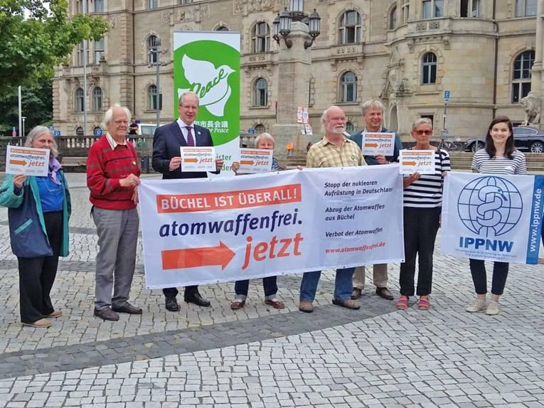 """Oberbürgermeister Stefan Schostok mit einer Gruppe von Personen vor dem Rathaus, die Transparente mit der Aufschrift """"atomwaffenfrei jetzt"""" halten."""