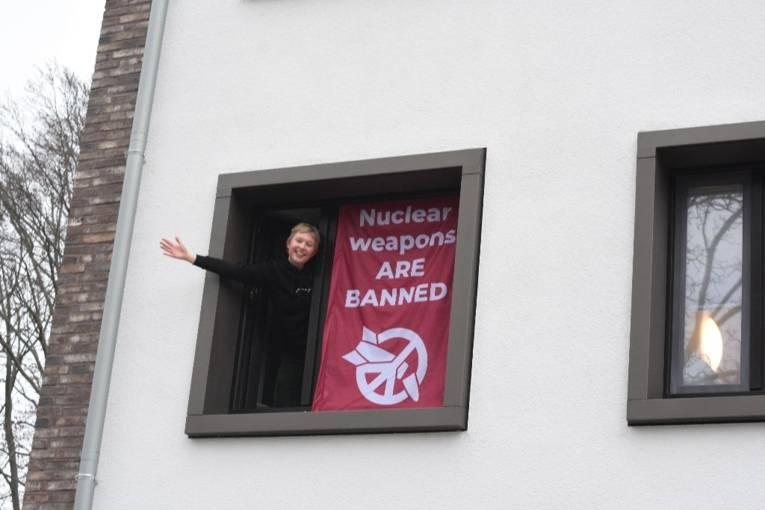 Mensch im Fenster mit Banner