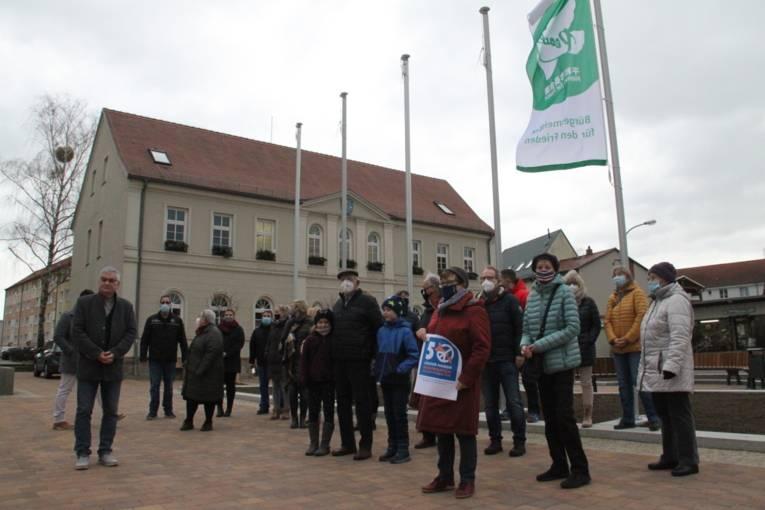 Menschen vor Gebäude mit Flaggen
