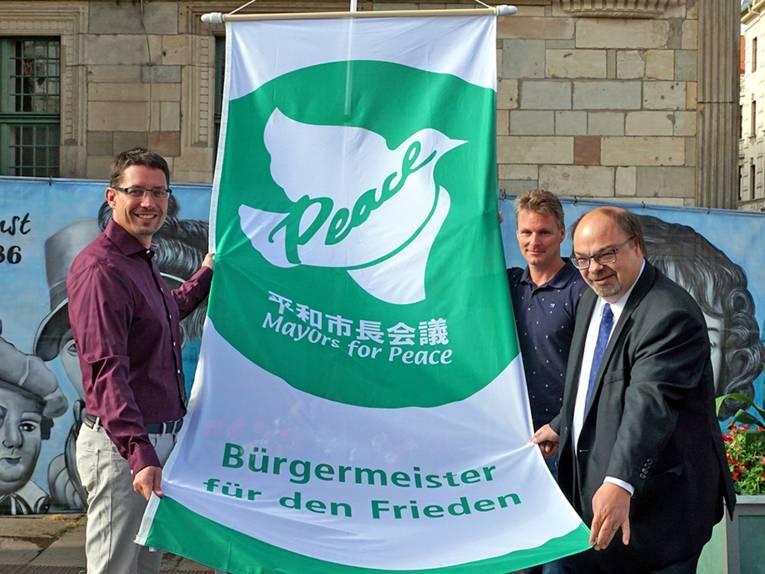 """Vor einem Gebäude halten drei Personen die Mayors for Peace Flagge so, dass man die weiße Taube auf grünem Grund und das Wort """"Peace"""" erkennen kann."""