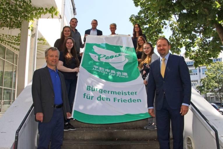 Mehrere Personen haben sich auf einer Treppe versammelt und zeigen die ausgebreitete Bürgermeister für den Frieden Flagge