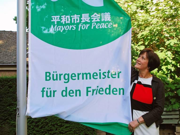 Oberbürgermeisterin Margret Mergen der Stadt Baden-Baden steht neben der gehissten Mayors for Peace Flagge