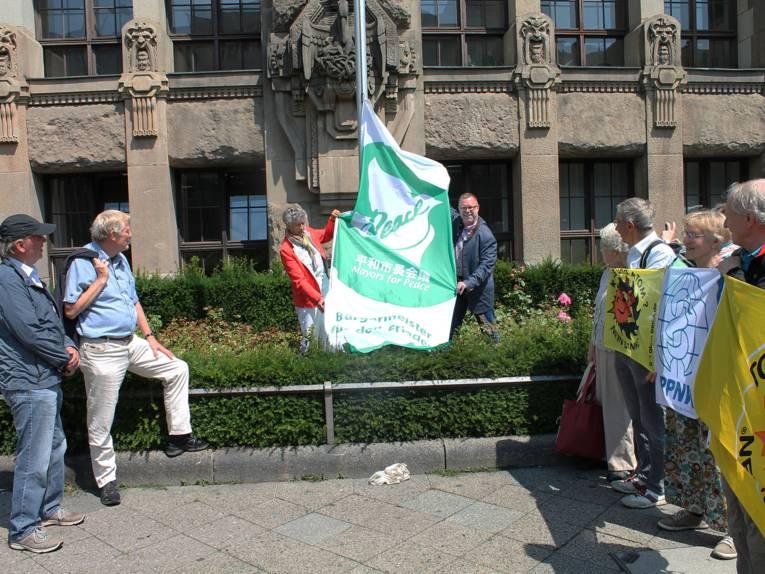 Vor einem historischen Gebäude wird im Beisein von Zuschauern die Mayors for Peace Fahne gehisst