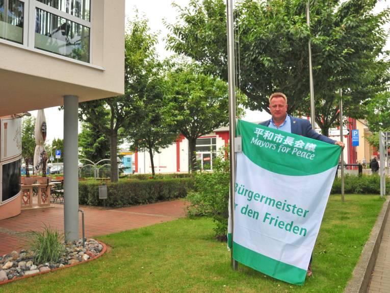 Bürgermeister Karsten Schneider hisst im Ostseebad Binz die Flagge der Mayors for Peace